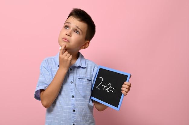 Симпатичный школьник, держащий доску с надписью мелом, задумчиво решает математическую задачу. изолированные на розовом фоне с копией пространства. обратно в школу. концепции