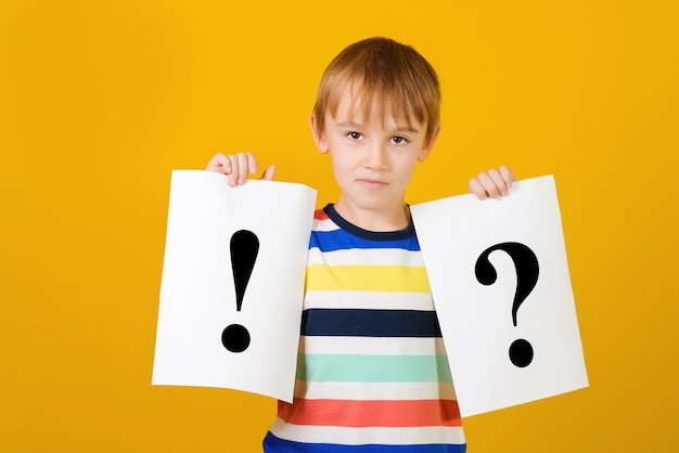 Cute schoolboy holding cards with question mark and exclamation point