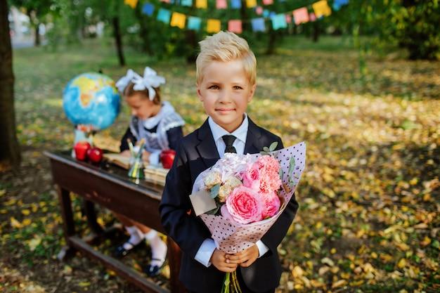 Симпатичный школьник в школьной форме держит букет