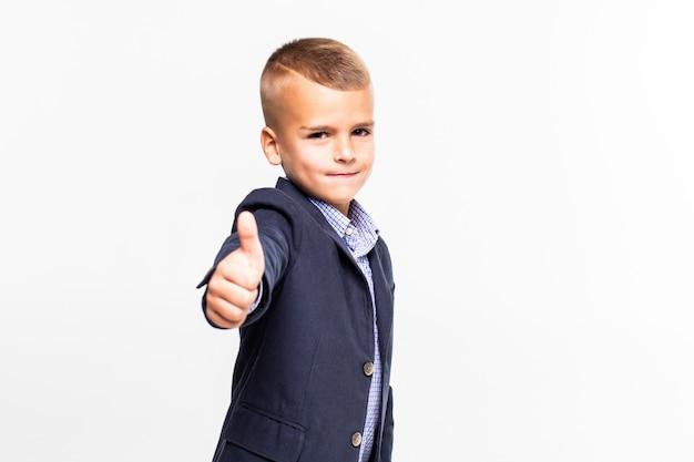 흰 벽에 고립 된 가입 엄지 손가락을 만드는 귀여운 소년