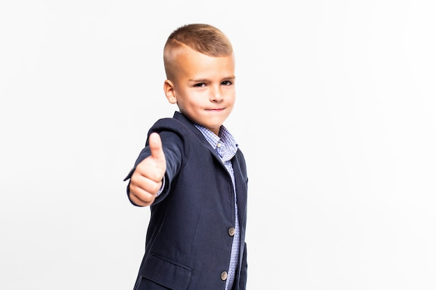 Cute schoolboy making thumbs up sign, isolated on white wall