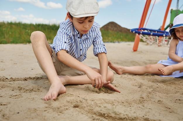 모래 놀이터에서 놀고 있는 귀여운 남학생은 모래에 녹색 새싹을 심습니다. 야외에서 놀기, 여름 휴가 개념. 여름 캠프