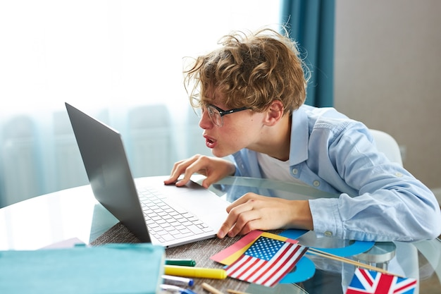 Cute schoolboy say hello at camera while having online lesson at home