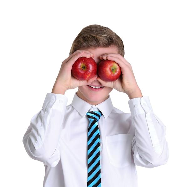 Милый школьник с яблоками на белой поверхности