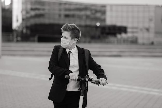 街でスクーターを運転する保護マスクを持つかわいい男子生徒。