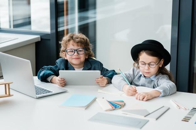 Симпатичный школьник с планшетом смотрит на вас, сидя за столом рядом с серьезным одноклассником, рисующим или делая заметки в тетради