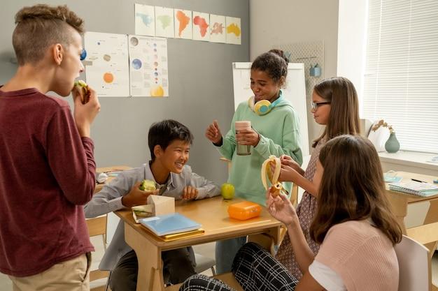 Симпатичные школьники перекусывают и обсуждают забавные вещи во время обеденного перерыва
