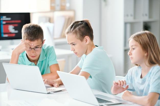 Симпатичные школьники сидят за партой в классе, работая над индивидуальными проектами после уроков