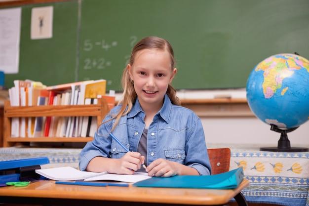 Cute schoolgirl doing classwork