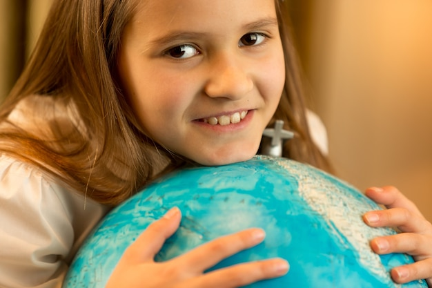 Cute schoolgirl holding big earth globe