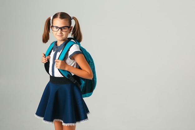 灰色の背景にカメラを見て青いバックパックとメガネのかわいい女子高生