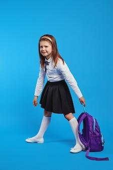 Симпатичная школьница в униформе держит тяжелый рюкзак на синем фоне