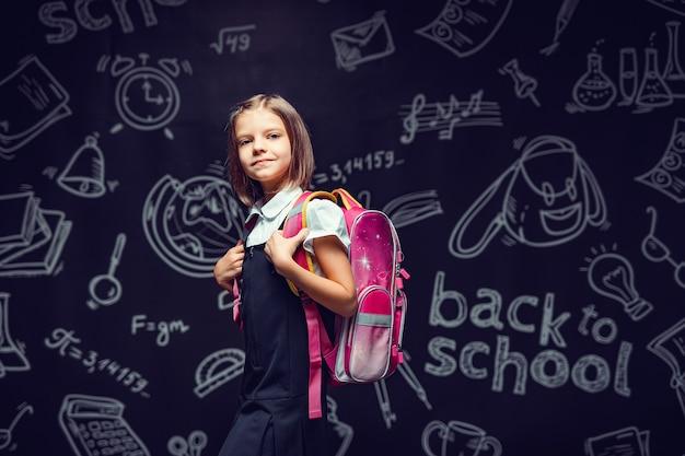 学校のコンセプトに戻るバックパックで学校に行く準備をしているかわいい女子高生