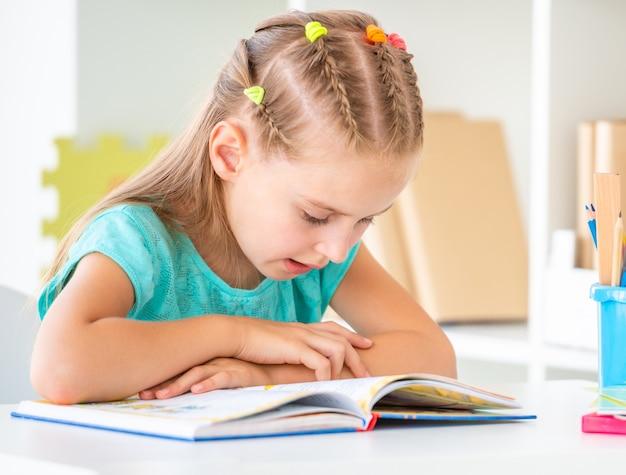 Cute schoolgirl reading book, closeup