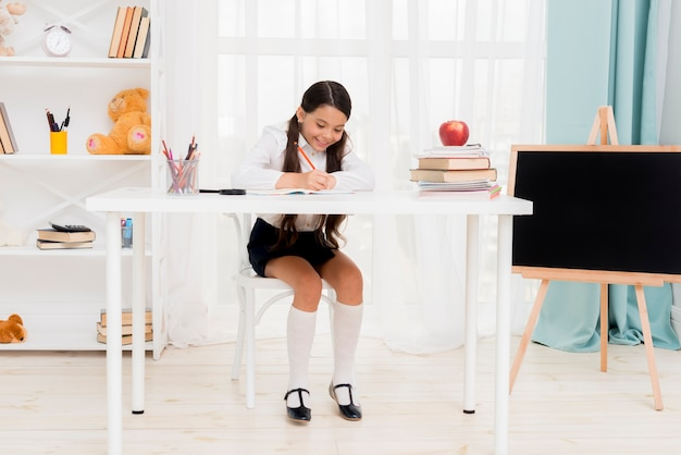 Cute schoolgirl sitting at desk and exercising in classroom