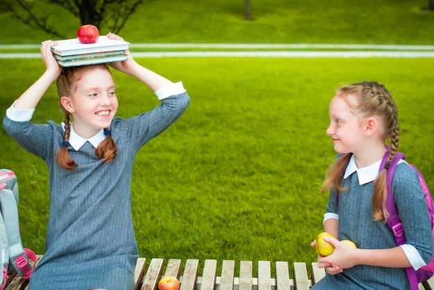 本とリンゴを頭に抱えて笑っているかわいい女子高生。学校に戻って幸せです。赤毛のおさげ髪。