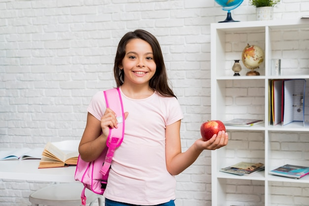 Cute schoolgirl standing with backpack and apple in classroom