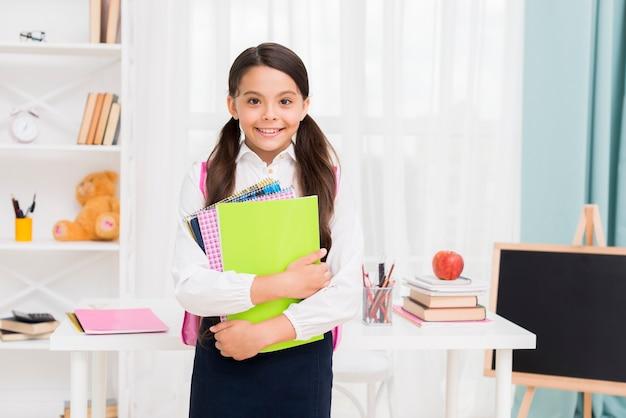 Cute schoolgirl in uniform holding notepads in classroom