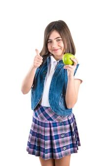 Милая школьница с яблоком на белом фоне.