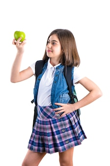 Cute schoolgirl with apple on white
