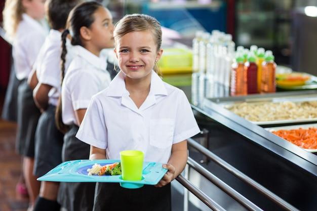 Cute schoolgirl with classmate standing near canteen counter