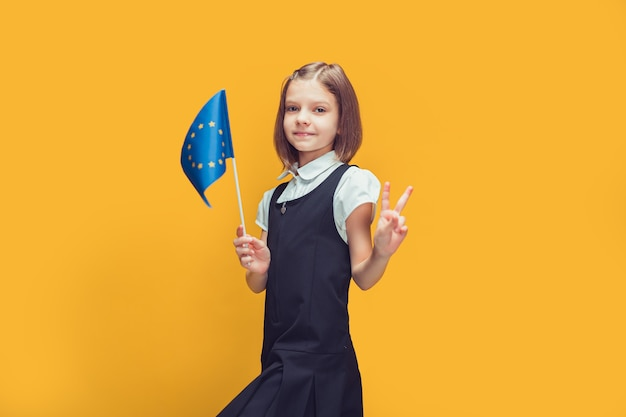 Cute schoolgirl with the flag of european union raising index finger up education in europe concept