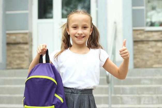 Cute schoolgirl with a school backpack in the schoolyard