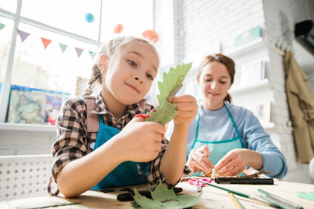 Cute schoolgirl with scissors cutting dry oak leaf while helping her teacher with decorations for holiday at lesson