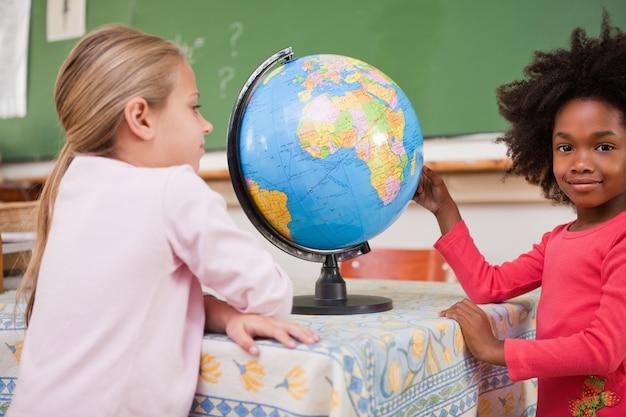 Cute schoolgirls looking at a globe