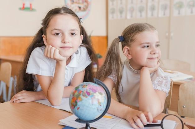 Cute schoolgirls sitting at desk