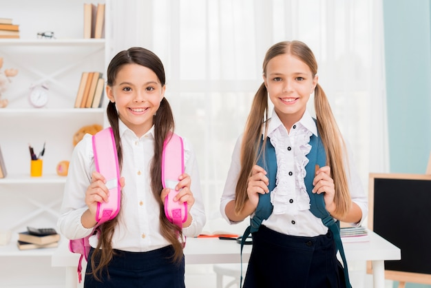 Cute schoolgirls with backpacks standing in classroom