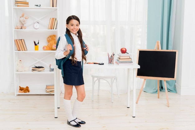 Cute schoolkid with backpack standing in front of desk at classroom