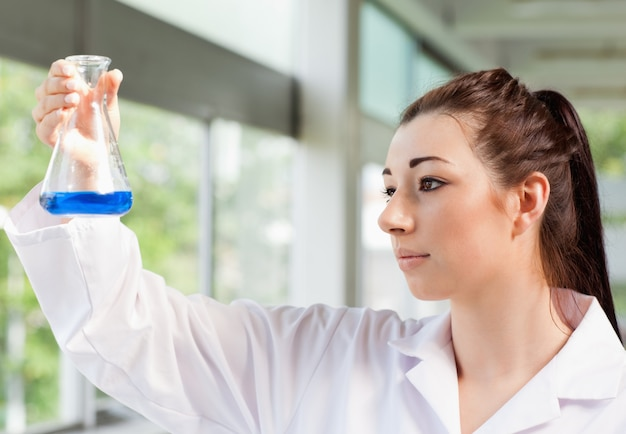 Cute science student looking at a blue liquid