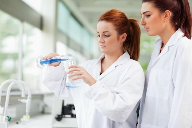 かわいい科学者がエルレンマイヤーフラスコに液体を注ぐ