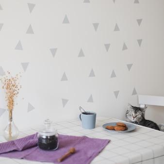 Милый шотландский гетеросексуальный кот и завтрак с чашкой чая и печеньем на столе