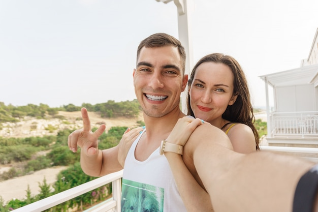 Cute selfie of a young couple hugging and smiling at the camera, a symbol of peace