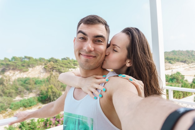 Cute selfie of a young married couple, a woman kissing the cheek of a man