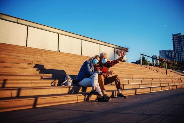 Милая пара пожилых людей сидит на лестнице на открытом воздухе во время пандемии вируса короны