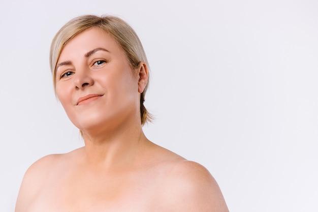 Милая старшая женщина с чистой кожей, глядя в камеру на белом фоне с боковым пространством. фото высокого качества