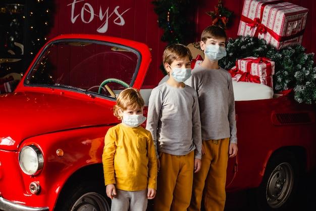 クリスマスの車の近くに立っている医療マスクのかわいい真面目な兄弟の男の子。