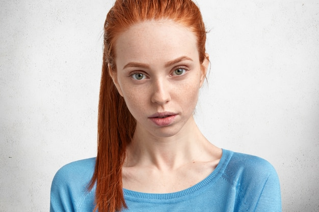 Cute serious female listens necessary information with attentive look, analyzes something in mind, has red hair and freckled face