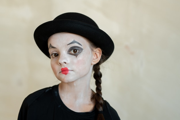 Cute serious girl with halloween makeup looking at you