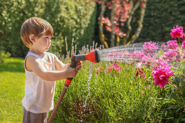 Cute serious little baby boy watering blooming flowers in garden from watering hose.