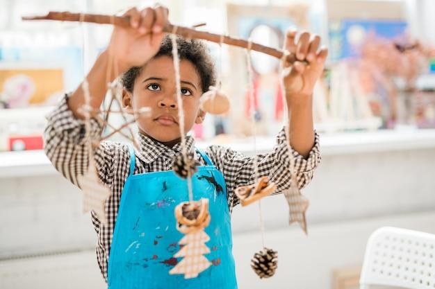 Симпатичный серьезный школьник в синем фартуке смотрит на палку с группой рождественских игрушек ручной работы и украшениями, висящими на нитках