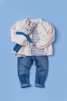 귀여운 가을 아동복 세트입니다. 파란색 배경에 장난감 토끼가 있는 재킷과 청바지.
