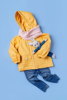 귀여운 가을 아동복 세트입니다. 파란색 배경에 장난감 토끼와 청바지가 있는 노란색 비옷. 가을 분위기