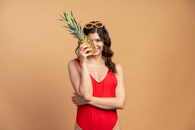 サングラスをかけたキュートでセクシーな女の子がパイナップルを手に持って顔に触れる