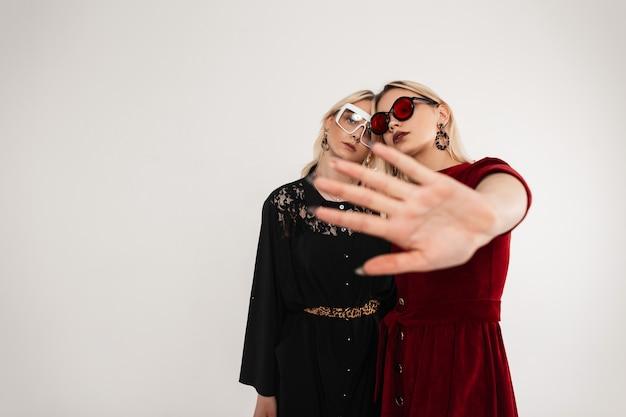 젊은 멋진 안경에 세련된 빨강-검정 옷을 입은 귀여운 섹시한 레즈비언 여성이 회색 벽 근처에 서 있습니다.