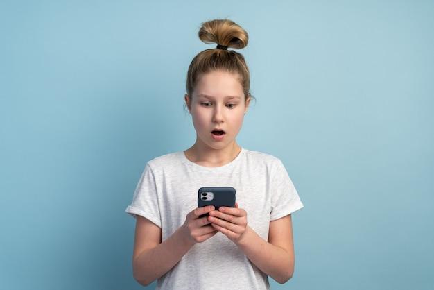 電話を見てかわいい、ショックを受けた十代の少女