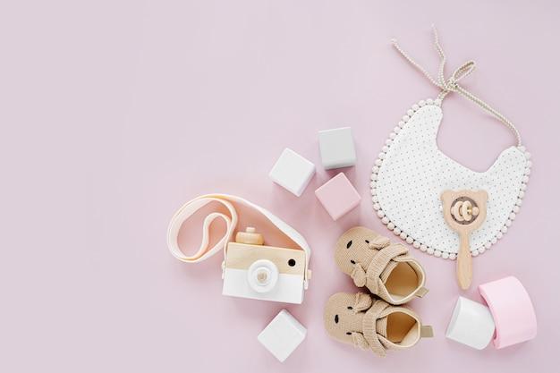 귀여운 신발, 턱받이 및 나무 장난감. 파스텔 핑크 배경에 소녀를 위한 아기 물건과 액세서리 세트. 베이비 샤워 개념입니다. 패션 신생아입니다. 평평한 평지, 평면도